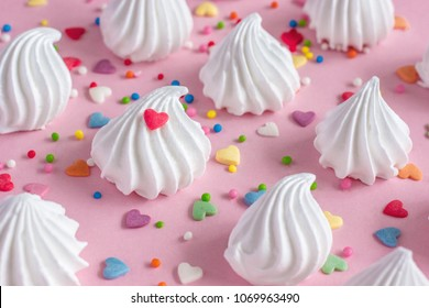 Crispy white twisted meringue and confectionery hearts on pink background. Concept love of sweet