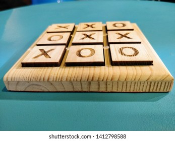 Criss cross board game made out of wood. X and o