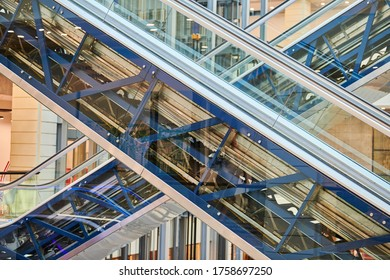 Crisscross escalators in shopping center. Empty escalators stairs up and down in office building, shopping mall or subway station.