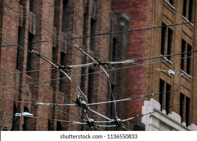 The crisscrossing of the power lines for electric city busses in downtown Seattle Washington with red brick buildings in the background.