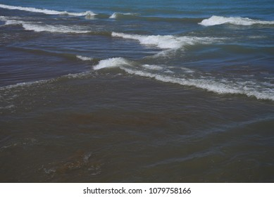 Crisscrossing wave pattern cause an X pattern in the water as the waves interfere with each other on a clear wavy spring day on Lake Michigan.