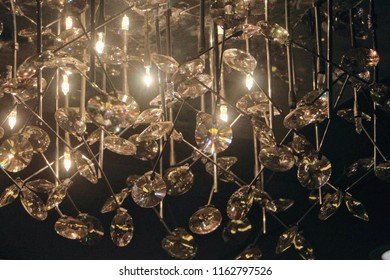 Cristal gems hanging with light bulbs in an intricate chandelier.