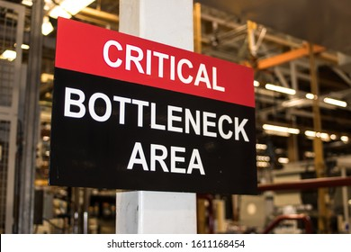 Critical Bottleneck Area sign in industrial factory setting