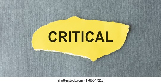 CRITICAL of the word on paper. concept. Words of CRITICAL on a wooden background.