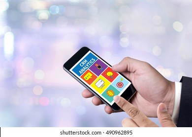 CRM ANALYTICS person holding a smartphone on blurred cityscape background
