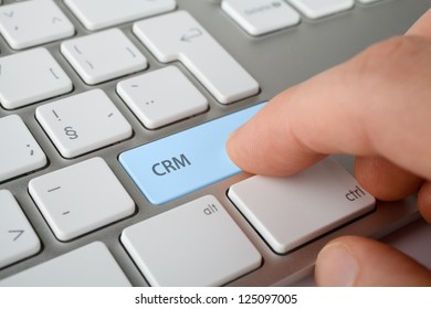 CRM (customer relationship management) concept. Man press CRM key on computer keyboard.