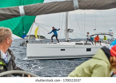 Croatia, Adriatic Sea, 19 September 2019: The race of sailboats, the team sits on the edge of a boat board, team work, intense fight, bright colors, other participants of race on a background