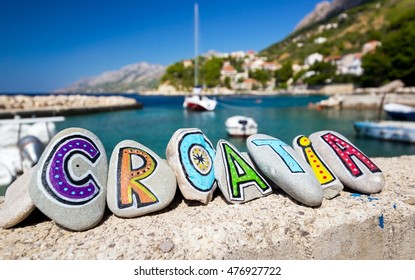 Croatia country name painted on the colorful stones, boat in background