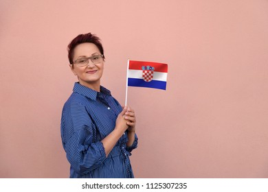 Croatia flag. Woman holding Croatian flag. Nice portrait of middle aged lady 40 50 years old with a national flag  over pink wall background.Learn Croatian language. Visit Croatia concept.