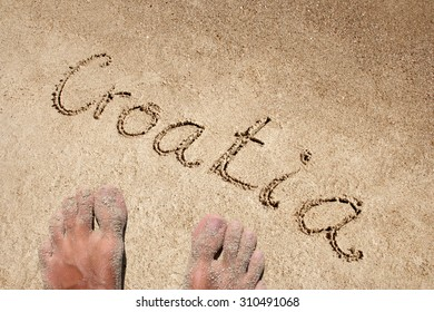 Croatia handwritten in sand on a beach background with feet in an exotic island for summer, ocean, sea, travel, vacation, tourism, tropical, coast, message, resort, paradise, sunny, water