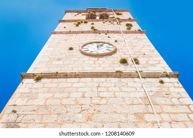 Croatia, island of Krk, Vrbnik, tower bell with old clock in old town, high stone building, sunny summer day