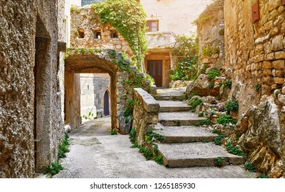 Croatia Istria. Ancient abandoned medieval town Plomin. Old stone street with ruined walls houses and stairs overgrown by ivy plants.