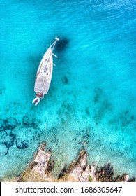 Primošten, Croatia - July 9 2019: Aerial top-down view on an isolated sailboat anchored near the shore in clear turquoise water
