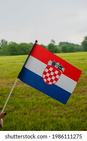 Croatia national hand flag on green meadow. National flag
