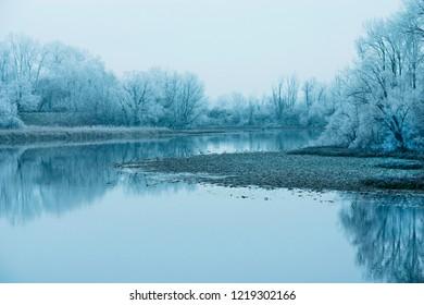 Croatia, nature park Lonjsko polje, reflection of trees under snow on frozen lake in winter