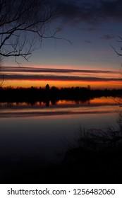 Croatia, nature park Lonjsko polje, beautiful red sunset over Sava river in autumn, reflection on water