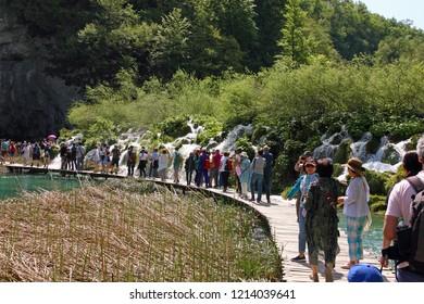 CROATIA PLITVICE, 29 APRIL 2018: Tourists walk on a path in Plitvice Lakes National Park, Croatia