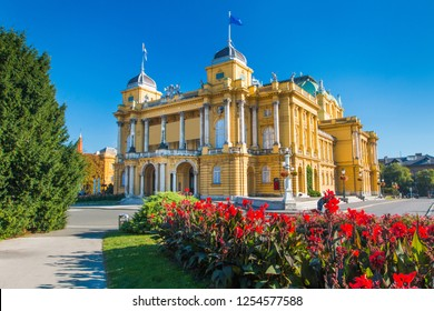 Croatia, Zagreb, beautiful historic national theater building and flowers in park, blue sky, summer day, popular tourist destination