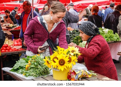 Croatia. Zagreb. September 12, 2013. Woman buying flowers at an outdoor market in Zagreb.