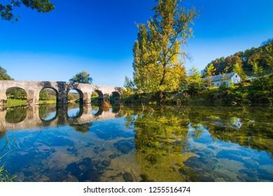 Croatian countryside, old stone bridge over the Dobra river in Novigrad, Karlovac county, beautiful landscape