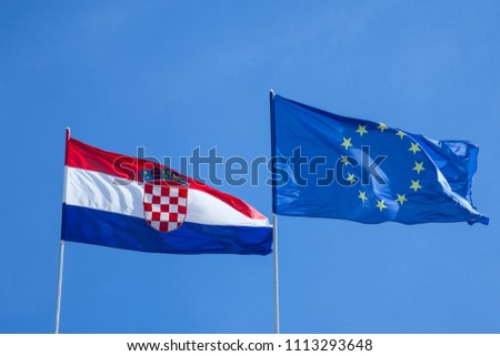 b93eeafd51 Croatian and European flags waiving in the air with a blue sky background.  Croatia is