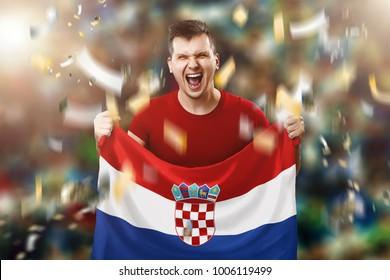 Croatian fan, a fan of a man holding the national flag of Croatia in his hands. Soccer fan in the stadium.