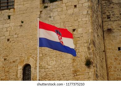 Croatian flag displayed against limestone outer walls of Trogir, Croatia