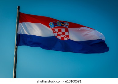 Croatian flag floating in the air with a blue background