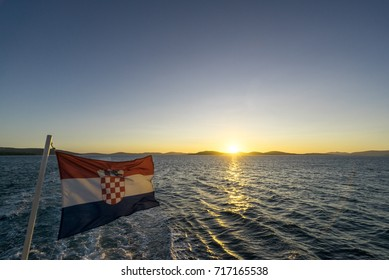 Croatian flag and sunset across islands from boat