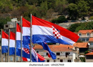 Croatian flags in a row, blowing in the wind. Defocused houses in the background. In Vela Luka, Korcula island, Croatia.