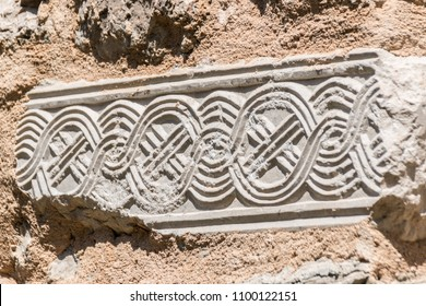 Croatian heritage 'pleter' carved in stone on a rustic abandoned church wall