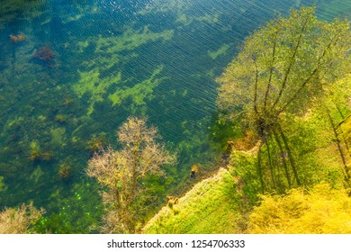 Croatian river Dobra from air, top down view from drone, Karlovac county, green surface of clear water in autumn, beautiful nature