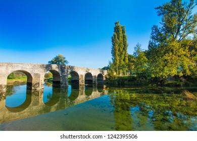 Croatian rivers, old stone bridge over the Dobra river in Novigrad, Karlovac county, beautiful countryside landscape