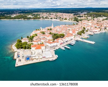Croatian town of Porec, shore of blue azure turquoise Adriatic Sea, Istrian peninsula, Croatia. Bell tower, red tiled roofs of historical buildings, boat, piers.  Euphrasian Basilica. Aerial view.