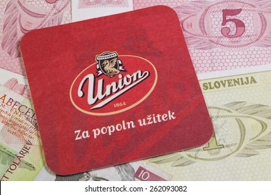 Croatia,Novigrad - August 13,2014: Beermat from Union beer and Slovenia money.The Union Brewery Ljubljana, Slovenia produces beer, refreshing non-alcoholic drinks and non-alcoholic drinks.