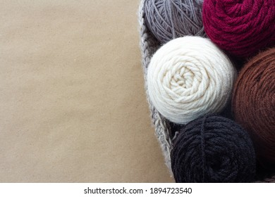 a crochet basket filled with burgundy, white, gray, black, brown yarn balls on a brown craft paper