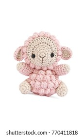 Crochet doll. A handmade crochet doll of a little lamb in pink isolated on a white background.