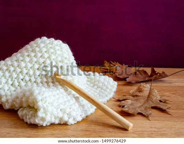 Crochet fall image with white crochet, bamboo crochet hook, fall leaves on a wooden table. Purple background. Room for copy.