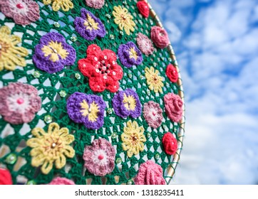 Crochet Flower decoration outdoors against a blue sky.
