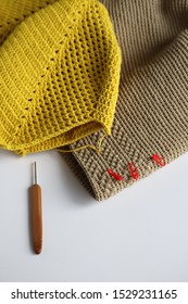 Crochet granny square bag and crochet brown bag with wood crochet needle on white background. Handmade crochet and craft.