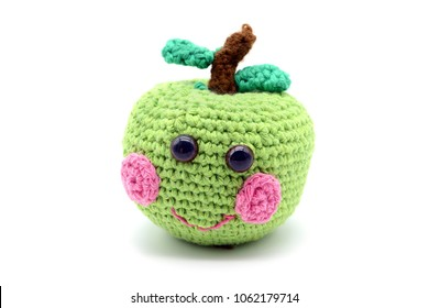 crochet green apple with smiling face on white isolated  background.