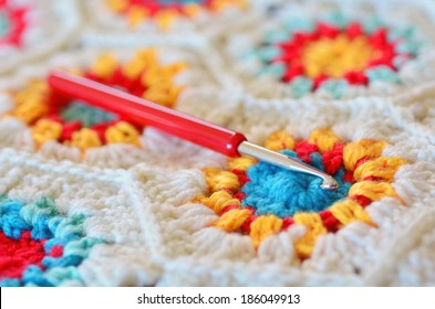 Crochet hook needle on granny square blanket. Concept photo of handmade art and crafts