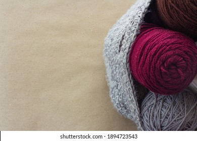crochet or knit bag full of burgundy brown gray and white yarn on craft paper