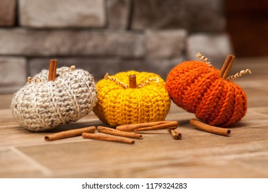 Crochet pumpkins in fall colors among cinnamon sticks.