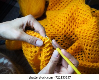 Crochet. Woman crochet yellow yarn on the dark background. Close-up of the hands.