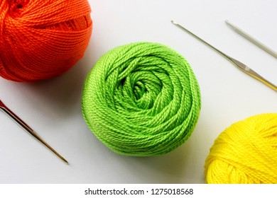 Crochet yarn background. Yarns green, red, yellow colors on white background with crochet hooks. Knitting, crochet supplies. Colorful cotton yarn for knitting. Handmade crocheting crafts & green yarn.