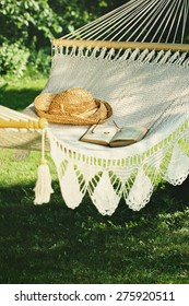 Crocheted hammock with straw hat and book