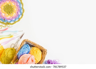 Crocheted home bright colored mat. Rainbow yarn in the basket. Hooks for knitting.