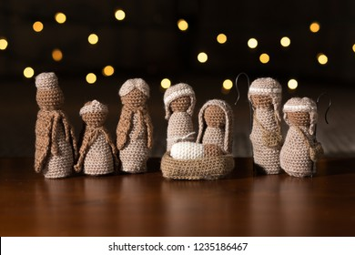 A crocheted set of baby Jesus in a manger with Mary, Joseph, three wise men, and two shepherds in a starlit scene.
