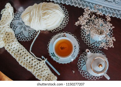 Crocheting out of white wool yarn on the table with white lace tablecloth and herbal tea, relax crafts hobby
